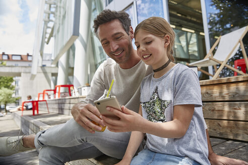 Happy father and daughter looking at cell phone at an outdoor cafe - SUF00214