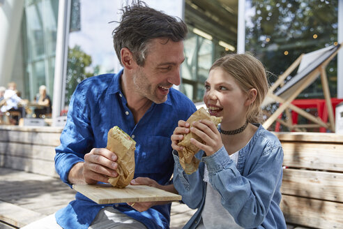 Father and daughter having a snack at an outdoor cafe - SUF00217
