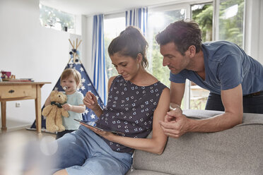 Couple using tablet at home with boy in background - SUF00232