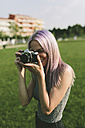 Young woman taking pictures with camera in nature - GIOF02904