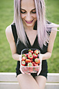 Smiling young woman holding  box of strawberries - GIOF02907