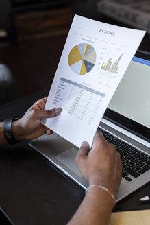Man analysing budget on sheet of paper - GIOF02916