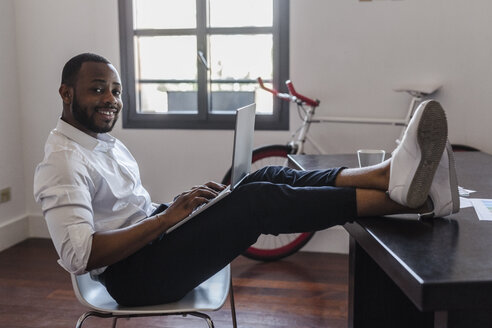 Man using laptop in home office with feet on desk - GIOF02922