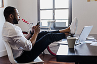 Man using cell phone in home office with feet on desk - GIOF02925
