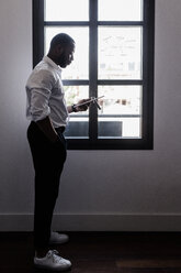 Businessman holding tablet at the window - GIOF02934