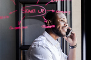 Smiling businessman on cell phone in office with writing on windowpane - GIOF02937