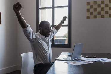 Happy businessman with laptop at desk raising his arms - GIOF02940
