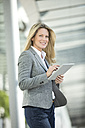 Smiling businesswoman using tablet outdoors - MAEF12272