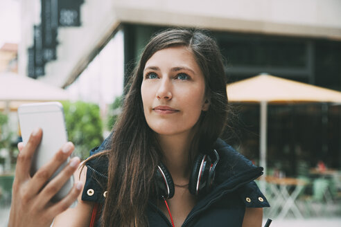 Young woman with cell phone and headphones in the city - CHAF01908