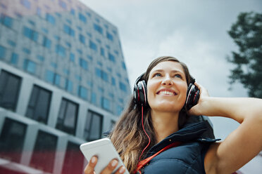 Smiling young woman with headphones and cell phone in the city - CHAF01914