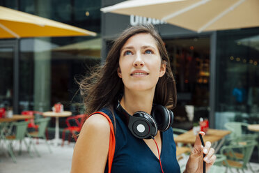 Portrait of smiling young woman with headphones and takeaway drink in the city - CHAF01917