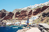 Greece, Santorini, Oia, woman enjoying the view in the fishing harbor with the white village above the cliff - GEMF01722
