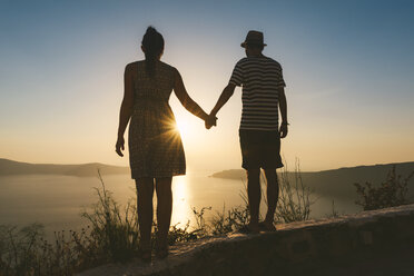 Greece, Santorini, Fira, couple holding hands and enjoying sunset over the Santorini caldera - GEMF01734