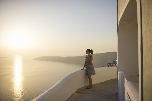 Greece, Santorini, Fira, woman enjoying the sunset - GEMF01737