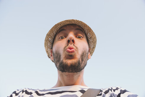 Man with straw hat kissing to the camera - GEMF01740