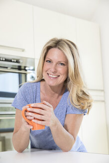 Portrait of smiling woman at home with cup of coffee - MAEF12284