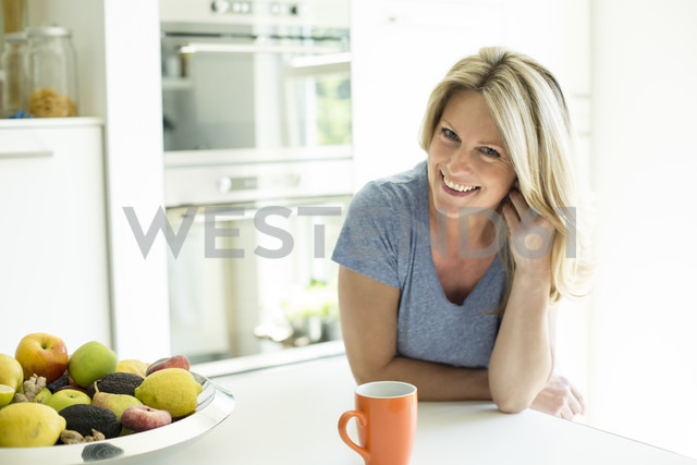 Portrait of smiling woman at home with cup of coffee and fruit bowl - MAEF12287