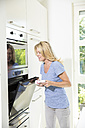 Woman in kitchen closing oven - MAEF12290