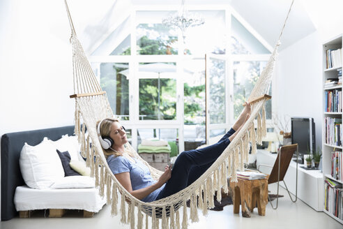 Relaxed woman at home lying in hammock listening to music - MAEF12293