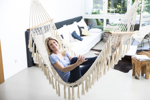 Relaxed woman at home lying in hammock - MAEF12296