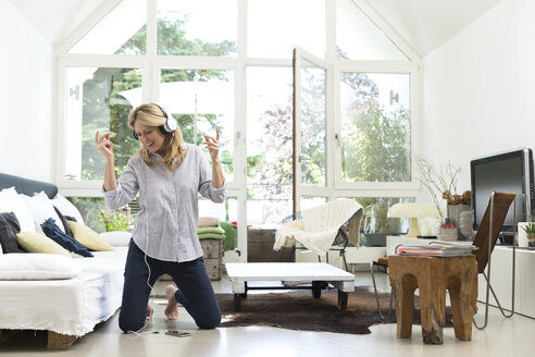 Excited woman at home listening to music - MAEF12302