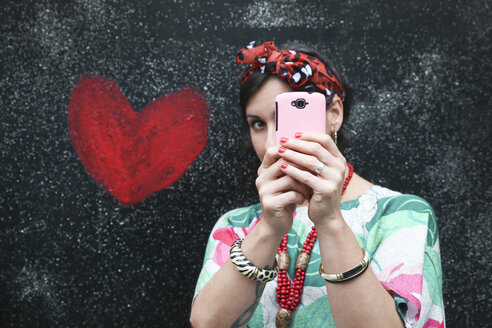 Woman taking a selfie next to heart painted on the wall - RTBF00986