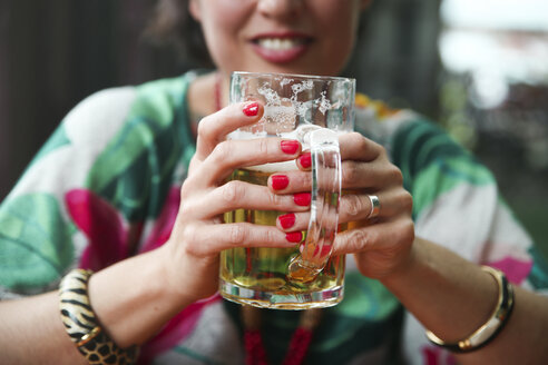 Close-up of woman holding a beer mug in a street restaurant - RTBF00992