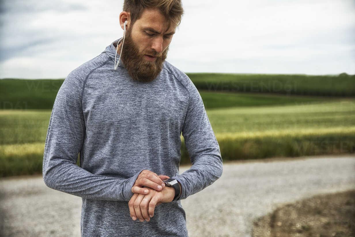 Man with earphones using smartwatch, standing outdoors - MAEF12313 - Roman Märzinger/Westend61