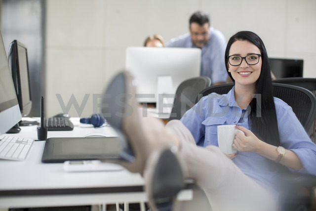 Office employee relaxing at her work station with coffee - ZEF14074