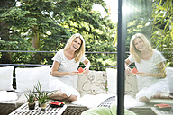 Mature woman sitting on balcony, eating water melon - MAEF12316