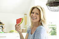 Mature woman sitting in kitchen, eating water melon - MAEF12319