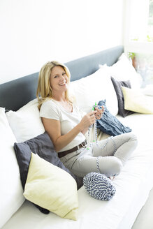 Mature woman sitting in living room, knitting - MAEF12331