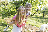 Two sisters having fun in garden - SHKF00759