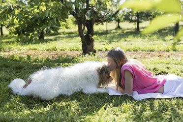 Girl lying with dog on meadow - SHKF00762