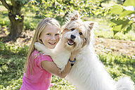 Girl playing with dog on meadow - SHKF00768