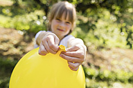 Girl holding balloon on meadow - SHKF00774