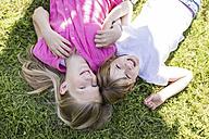 Two happy sisters lying in meadow - SHKF00777