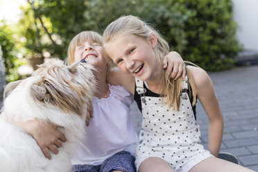 Two happy sisters cuddling with dog in the yard - SHKF00783