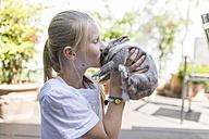 Girl kissing rabbit outdoors - SHKF00786