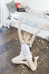 Girl at home sitting on floor throwing confetti - SHKF00792