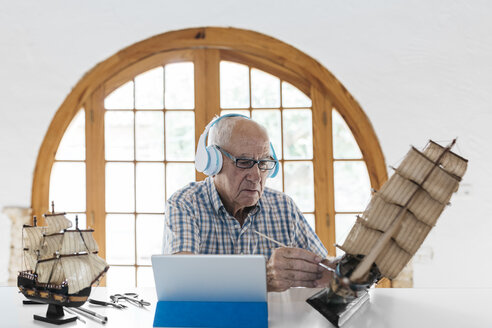 Senior man wearing headphones painting model ship on table with tablet - JRFF01405