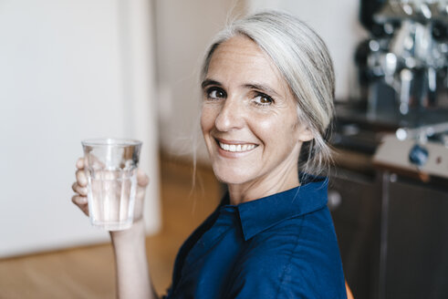 Portrait of smiling businesswoman holding glass of water - KNSF01773
