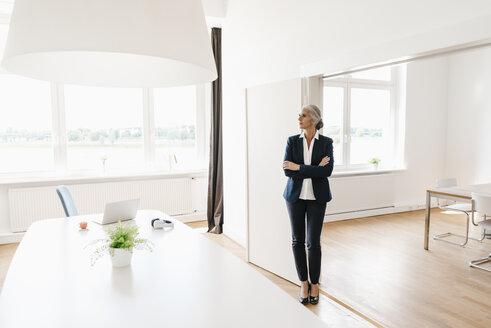 Businesswoman standing in modern office - KNSF01776