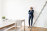 Businesswoman standing in modern office - KNSF01779