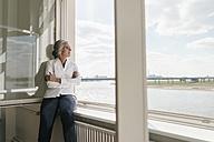Businesswoman in office looking out of window - KNSF01788