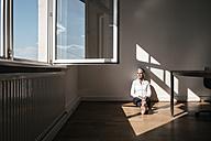 Businesswoman sitting on floor in office - KNSF01791