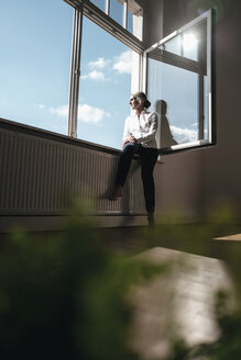 Businesswoman in office looking out of window - KNSF01794