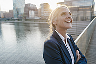 Smiling businesswoman on bridge looking up - KNSF01797