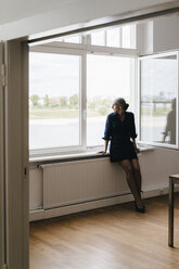 Businesswoman sitting on windowsill - KNSF01809