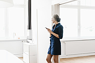 Businesswoman in office looking out of window - KNSF01812